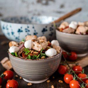Mediterraner Brotsalat mit Brot, Tomaten und Mozzarella in einer Schüssel.