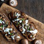 Schwarzwaldkruste Brot mit karamellisierten Zwiebeln und Pilzen angerichtet auf einem Holzbrett.